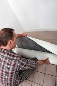 Crouching man unrolling flooring
