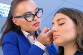 Makeup Artist Glue Artificial Eyelashes To Girl In Beauty Salon. Professional Visagiste Making Exten poster