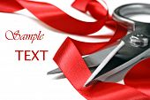 Shiny red satin ribbon curled around stainless steel scissors on white background with copy space.