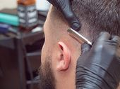 Hairstylist Shaving Clients Head With Open Razor, Close Up View. Stylists Hands In Black Rubber Glov poster