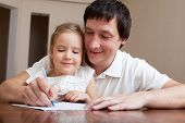 stock photo of time study  - Father helping daughter doing homework - JPG