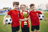 Three Happy Cheerful Kids Of Sports Soccer Team. Boys Football Players Holding Trophy At The Stadium poster