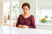 Young beautiful african american woman at home depressed and worry for distress, crying angry and af poster
