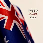 closeup of some australian flags and the text happy flag day against a beige background poster