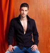 Latin spanish man portrait open black shirt with curtain and orange vintage background
