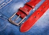 Red Leather Belt And Blue Jeans Close-up. A Belt Lying On Denim. Fashionable Red Belt Close-up. poster