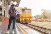 Young Woman Traveler With Backpack Looking To Map While Waiting For The Train.holiday, Journey, Trip poster