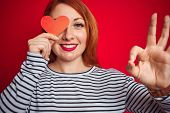 Young redhead romantic woman holding heart over red isolated background doing ok sign with fingers,  poster