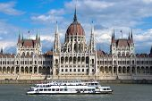 Budapest: a sightseeing boat passes in front of the symmetrical building of the Hungarian Parliament