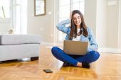 Beautiful young woman sitting on the floor with crossed legs using laptop stressed with hand on head poster