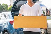 Closeup Of Happy Asian Man Delivering Cardboard Box To Customers Via Private Car. People Lifestyles  poster