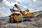 image of shovel  - Loading of iron ore on very big dump - JPG