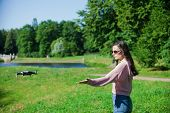 Walk With A Drone. A Woman In Black Glasses Launches A Low Flying Drone Into The Air, Catches A Flyi poster