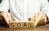 Businessman Puts Wooden Blocks With The Word Goal. The Concept Of Achieving Business Goals. Reaching poster