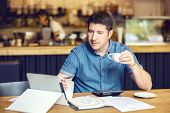 Successful New Restaurant Owner Checking Monthly Reports Online On Tablet - Middle Aged Man Calculat poster