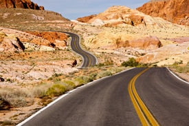 foto of long winding road  - a long and winding road through colorful desert sandstone  - JPG