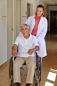 Geriatric nurse with senior man in wheelchair in a nursing home