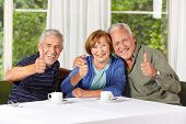 Happy senior people holding thumbs up while drinking coffee in retirement home