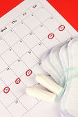 Menstruationskalender mit Hygieneartikeln und Tampons, close-up