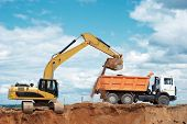 stock photo of boom-truck  - wheel loader excavator machine loading dumper truck at sand quarry - JPG