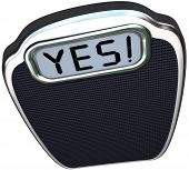 The word Yes on the digital display of a scale to give you positive results after diet or weight los