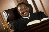 HAppy African American judge holding mallet in courtroom