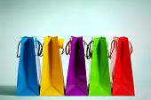 five colorful shopping bags in a row