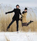 Man And Woman Jump On Lake Beach