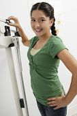 Portrait of teenage girl standing on weighing machine