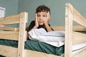 stock photo of bunk-bed  - Tired little boy lying on bunk bed - JPG