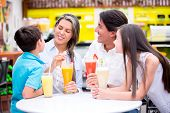 Happy family at a cafeteria drinking juices