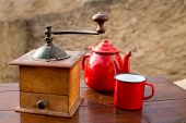 retro old coffee grinder with vintage teapot and red cup