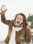 Happy Young Woman Throwing Snow Ball In Winter Park