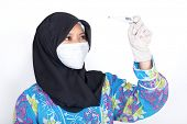 Young Muslim nurse checking temperature on thermometer