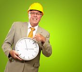 Portrait Of A Senior Man Holding A Wall Watch On Green Background