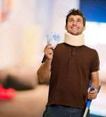 foto of neck brace  - Disabled Man With Neck Brace Holding Euro Note On Wooden Background - JPG