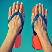 someone wearing flip-flops on his hands over the blue sky