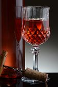 Closeup of a cut crystal glass of red wine and bottle against a light to dark gray background.