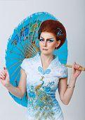 Geisha In A Smart Dress With Umbrella