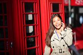 London woman taking on smart phone by red phone booth. Young casual female business woman walking wi