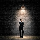 Image of young businesswoman standing under spot of light