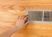foto of furnace  - Horizontal photo of female hand opening up heater floor vent with Red Oak Floors in background - JPG
