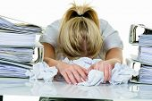 stock photo of shy woman  - a young woman desperately in office between many file folders and crumpled papier - JPG