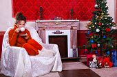 Woman With A Cup Of Tea Inside A Red Vintage Room Next To A Christmas Tree