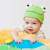 stock photo of baby frog  - cute baby playing in the frog hat lying on his stomach on a white background - JPG