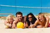 Group of friends - women and men - playing beach volleyball, they having a break and lying in the su