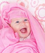Closeup portrait of cute newborn girl, sweet little baby covered with beautiful pink shawl, funny ch