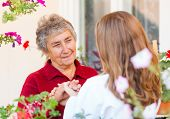 stock photo of hospice  - Happy elderly woman talking with her caregiver - JPG