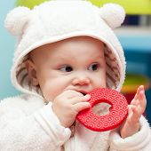 Little Baby Baby Chews On A Soft Plastic Toy In White Bear Costume