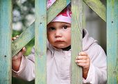 Brown Eyed Baby Girl In Pink Hat Plays With Old Green Wooden Wicket